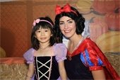 Young girl dressed as princess smiling next to woman in snow white costume